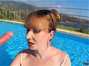 brit Mature red hard-core blowing lollipop in a pool